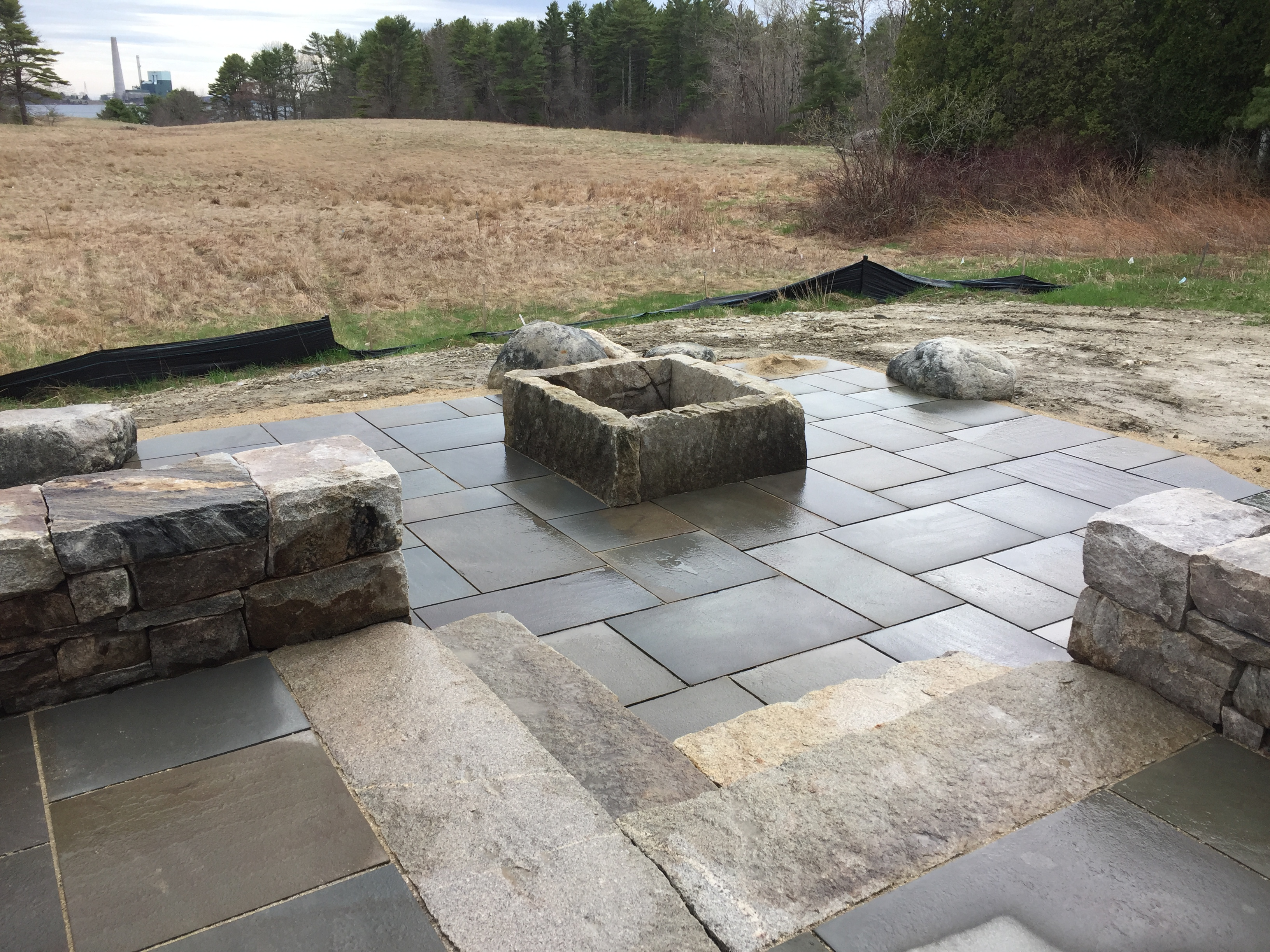 A Dry Laid Granite Sitting Wall Retains The Upper Level Of This Bluestone  Patio. On The Lower Level Four Large Slabs Of Granite Make A Simple Housing  For A ...